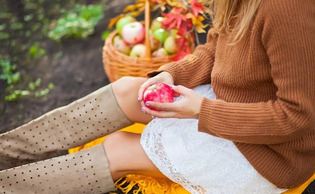 Femme avec une pomme mûre dans une main, assise sur une couverture jaune Photo Premium