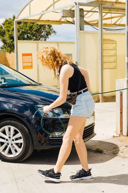 Femme, pompage, pneu, voiture, station essence Photo gratuit