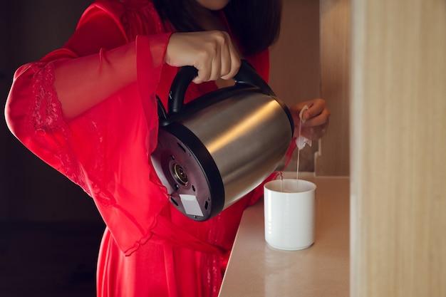 La Femme Portait Une Longue Robe En Satin Rouge Pour Faire Du Thé Dans La Cuisine La Nuit. Fille Asiatique Verser De L'eau Chaude Dans Une Tasse Blanche Photo Premium
