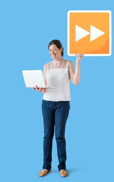 Femme portant un bouton d'avance rapide et un ordinateur portable Photo gratuit