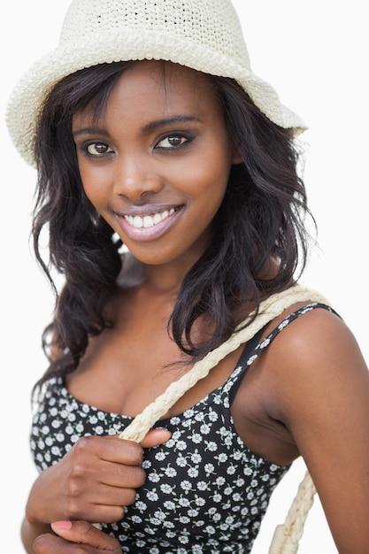 Femme portant chapeau d'été et robe de fleur noire sur fond blanc Photo Premium