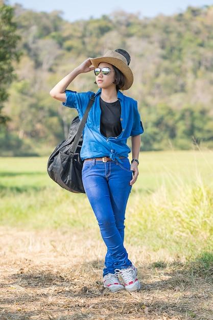 Femme portant un chapeau marchant et portant son sac de guitare Photo Premium