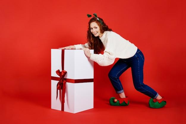 Femme Portant Un Grand Cadeau De Noël Photo gratuit