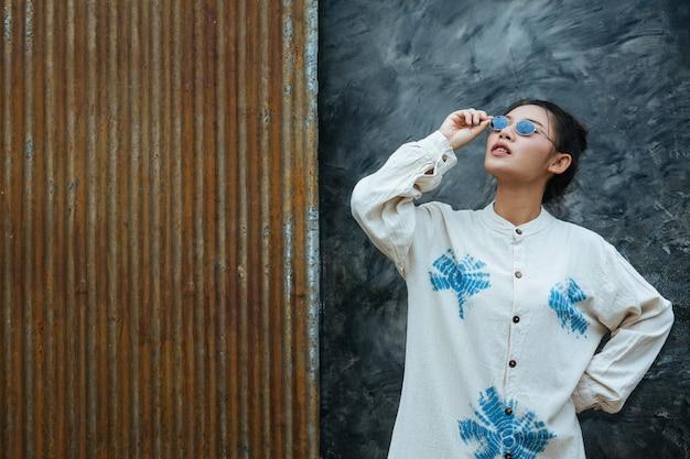 Une femme portant des lunettes indique que le ciment est gris et rouille. Photo gratuit