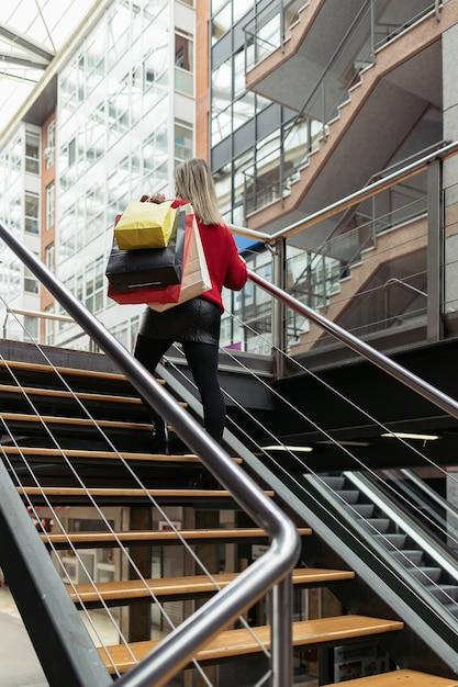 Femme Portant Un Pull Rouge En Montant Les Escaliers D'un Centre Commercial Transportant Des Sacs à Provisions. Photo Premium
