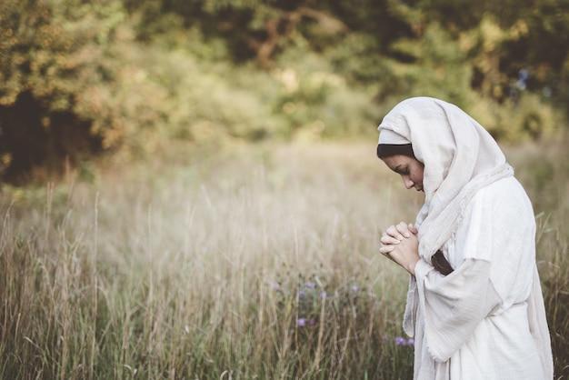 Femme Portant Une Robe Biblique Et Priant Alors Que Ses Yeux Sont Fermés Photo gratuit