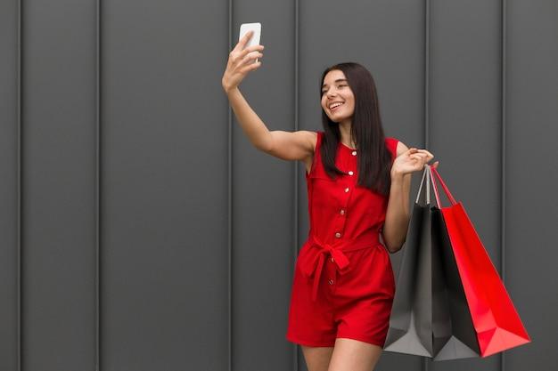 Femme Portant Des Sacs à Provisions En Prenant Une Photo De Soi Photo gratuit