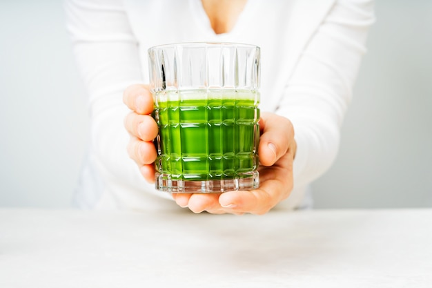 Femme portant des vêtements blancs tenant le verre avec du thé japonais matcha ou un smoothie vert Photo Premium