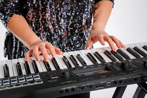 Une femme porte un chemisier brillant et pose avec un clavier de piano. isolé sur blanc Photo Premium