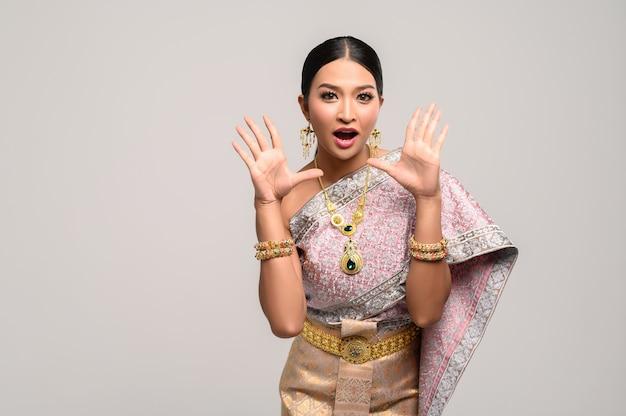La femme porte des vêtements thaïlandais et ouvre les mains des deux côtés. Photo gratuit