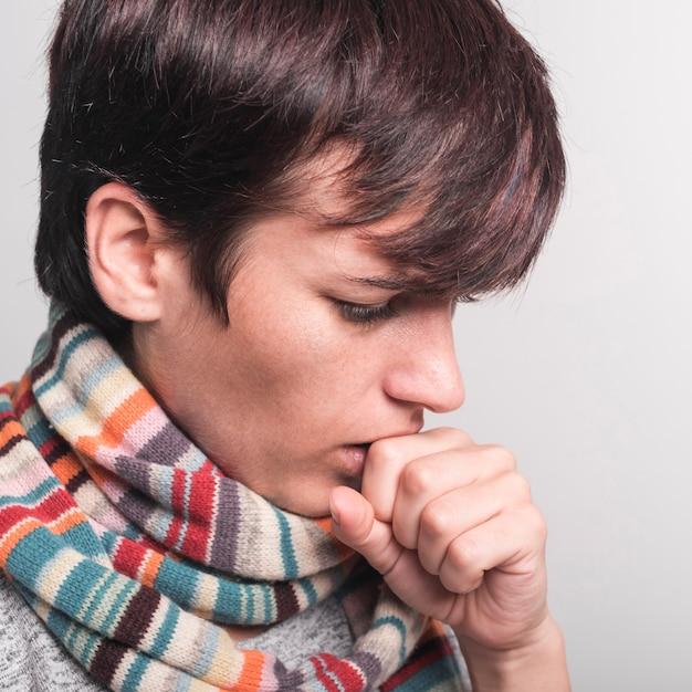 Femme, porter, écharpe multicolore, autour de, cou, tousser, contre, toile de fond grise Photo gratuit