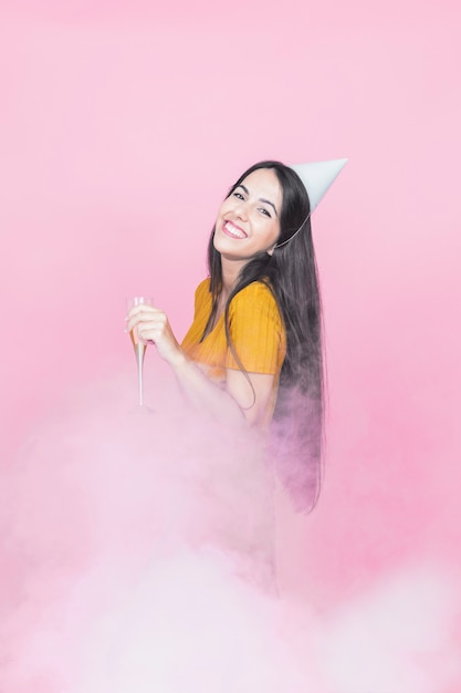 Femme, porter, fête, chapeau, tenue, champagne, flûte, debout, fumée, contre, fond rose Photo gratuit