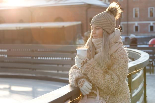 Femme Porter Des Mitaines Blanches Tenant Une Tasse Blanche Fumante De Café Chaud Ou De Thé En Froide Journée Ensoleillée D'hiver Photo Premium