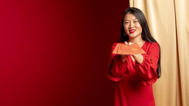 Femme posant avec des cartes de nouvel an chinois Photo gratuit