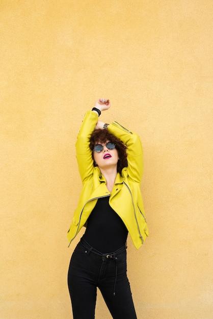 Femme posant sur fond uni Photo gratuit