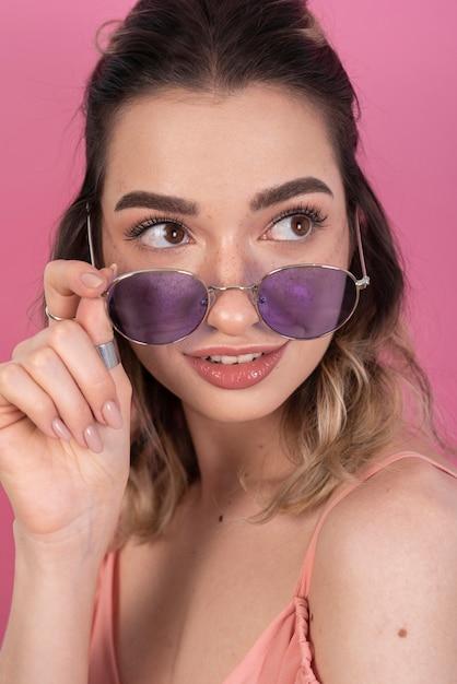Femme posant avec des lunettes violettes Photo gratuit