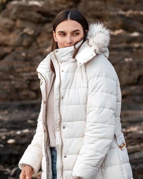 Femme Posant à La Plage Avec Veste D'hiver Photo gratuit
