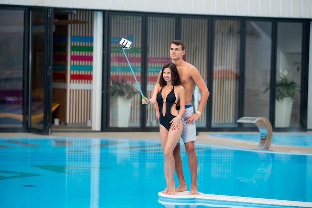 Femme posant près de la piscine fait une photo de selfie avec un bâton de selfie Photo Premium