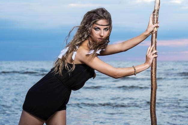 Femme pose avec un bâton Photo gratuit