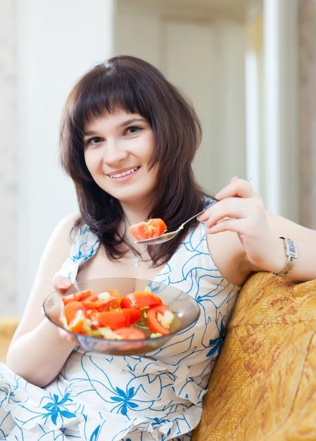 Femme positive mange salade végétarienne Photo gratuit