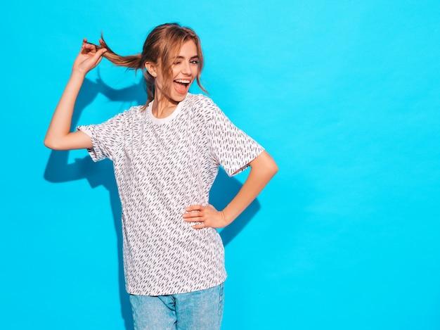 Femme Positive Souriant. Modèle Drôle Posant Près Du Mur Bleu En Studio. Photo gratuit