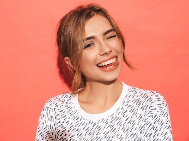 Femme Positive Souriant. Modèle Drôle Posant Près Du Mur Rose En Studio. Montre La Langue Et Les Clins D'œil Photo gratuit
