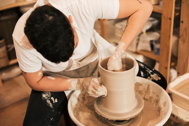 Femme potier accrochant le pot sur le tour de potier dans l'atelier Photo gratuit