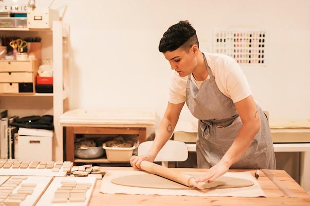 Femme potier aplatissant l'argile avec un rouleau à pâtisserie sur une table en bois Photo gratuit
