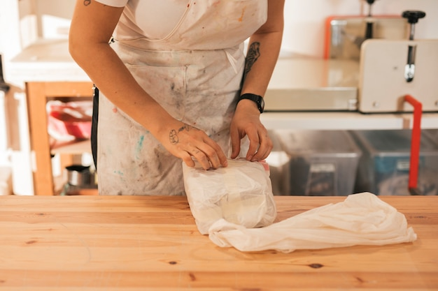 Femme potier déballant l'argile dans l'atelier Photo gratuit