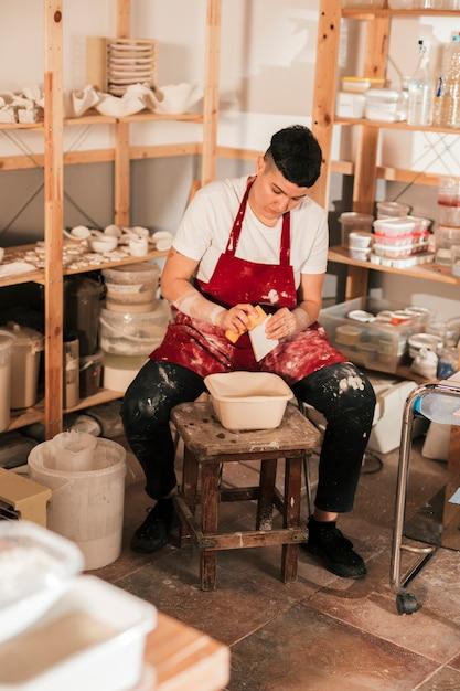 Femme potier essuyant les petits carreaux avec une éponge dans l'atelier Photo gratuit
