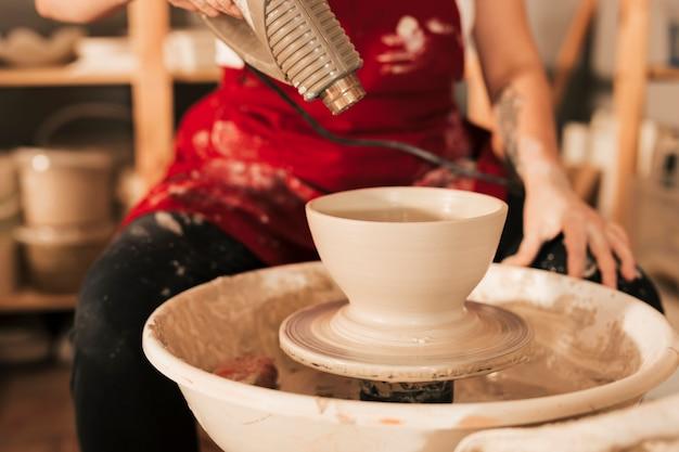 Une femme potière avec un sèche-cheveux sèche un bol en argile Photo gratuit