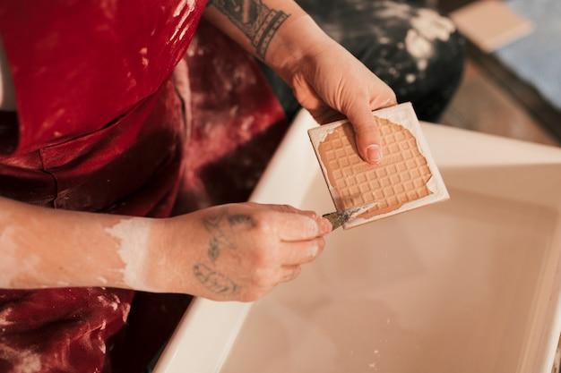 Femme potter enlever la peinture avec des outils tranchants sur la baignoire Photo gratuit