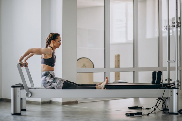 Femme pratiquant le pilates dans un reformeur de pilates Photo gratuit