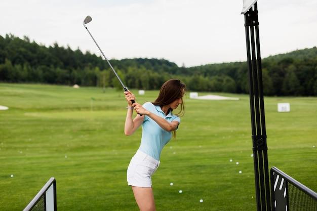 Femme pratiquant le swing de golf à l'extérieur Photo gratuit