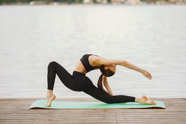 Femme Pratiquant Le Yoga Avancé Au Bord De L'eau Photo gratuit