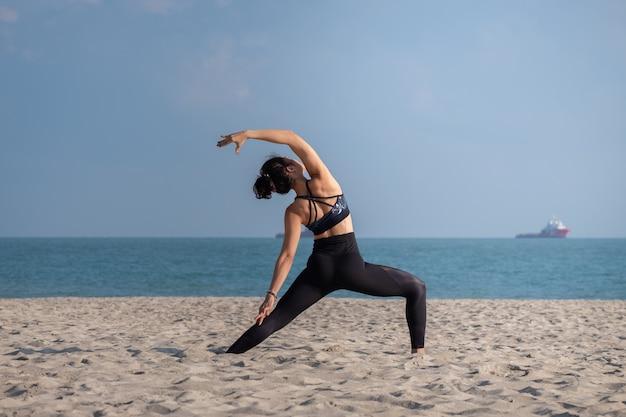 Une femme pratiquant le yoga sur la plage Photo Premium