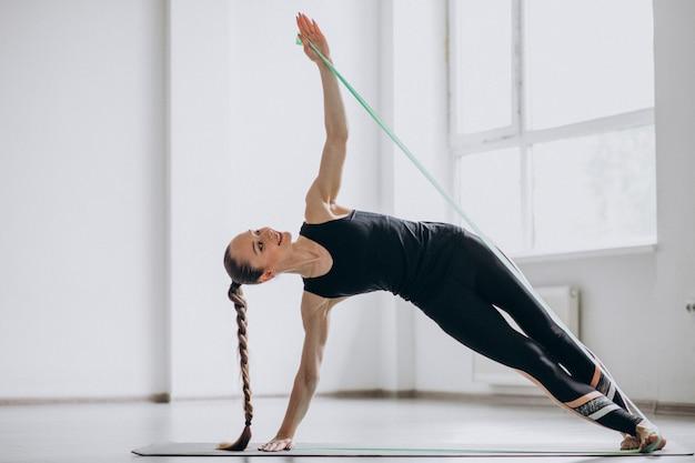 Femme pratiquant le yoga sur un tapis Photo gratuit