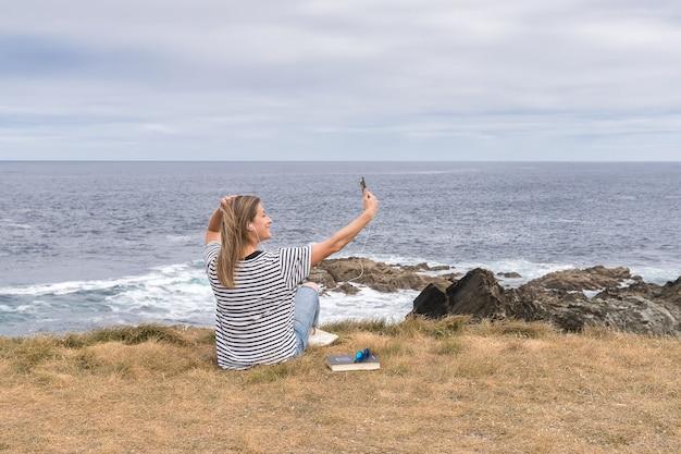 Femme Prenant Un Autoportrait Avec Un Téléphone Portable Assis En Face De La Mer. Photo Premium