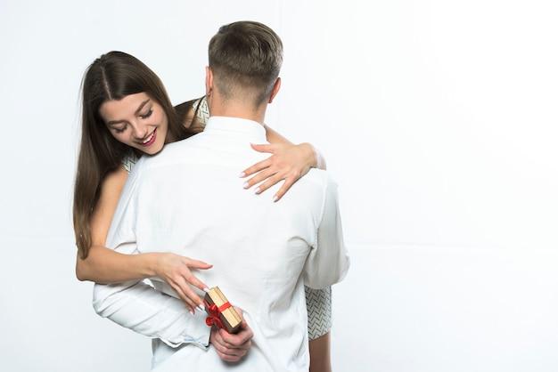 Femme prenant cadeau derrière homme dos Photo gratuit