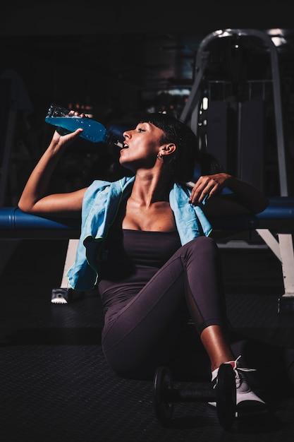 Femme prenant une pause en salle de sport Photo gratuit