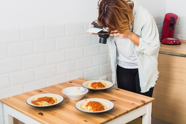 Femme prenant la photo des assiettes de nourriture Photo gratuit