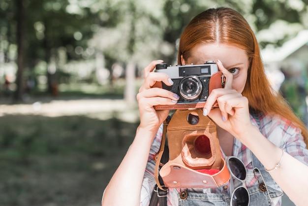 Femme prenant une photo avec caméra Photo gratuit