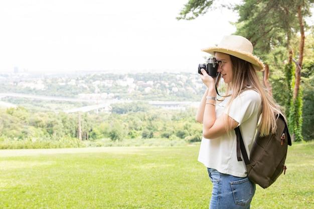 Femme prenant une photo sur le côté Photo gratuit