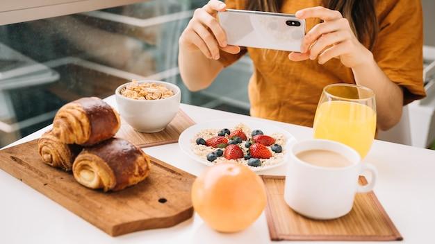 Femme Prenant Une Photo Du Petit Déjeuner à La Table Blanche Photo gratuit