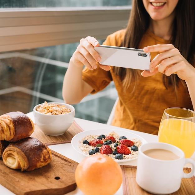 Femme Prenant Une Photo Du Petit Déjeuner à La Table Photo gratuit