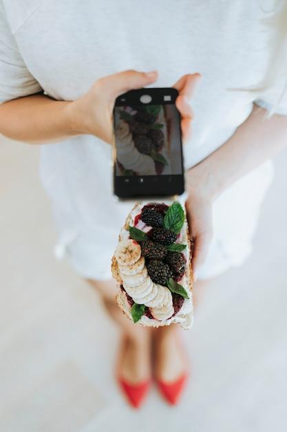Femme prenant une photo d'un pain grillé avec de la confiture de mûres et du fromage à la crème végétalien Photo gratuit