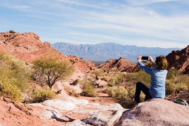 Femme prenant une photo d'un paysage de montagne Photo gratuit