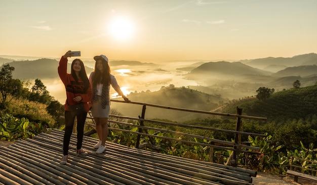 Femme prenant une photo avec un smartphone au sommet de la montagne Photo Premium