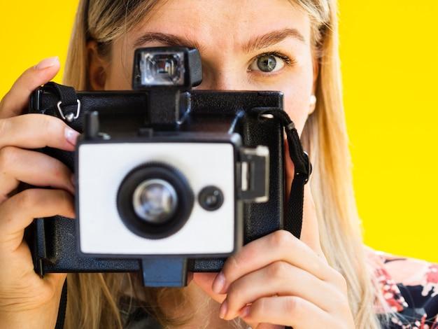 Femme prenant des photos avec un appareil photo rétro Photo gratuit