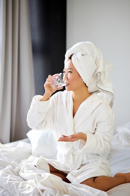 Femme Prenant Des Pilules Et Un Verre D'eau Pour Le Traitement, Le Matin. Belle Femme Boit Des Vitamines Pour La Prévention Des Maladies. Concept De Bien-être Et De Santé Photo Premium